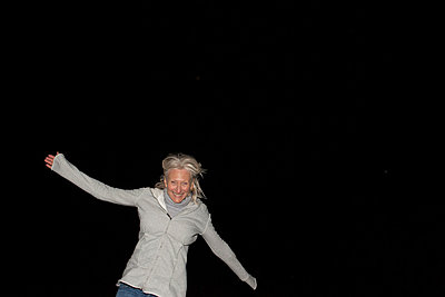 Portrait of mature woman with arms out at night - p924m821670f by Sean Murphy