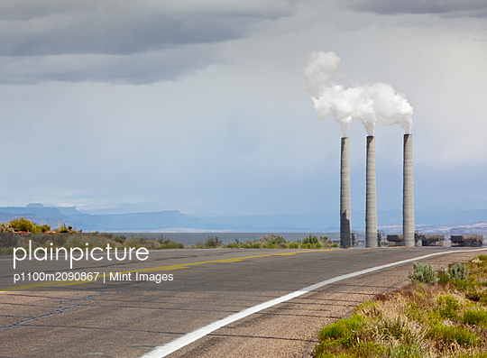 Desert Road Leading Towards Smokestacks - p1100m2090867 by Mint Images