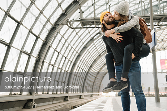 Happy young couple having fun and kissing at the station platform, Berlin, Germany - p300m2154527 by Hernandez and Sorokina