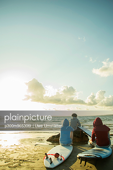 Three teenagers sitting on the beach watching sunset - p300m965306f by Uwe Umstätter