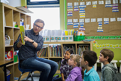 Elementary students listening to teacher read in classroom - p1192m1016755f by Hero Images
