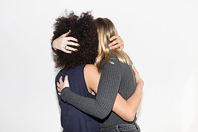 Two young women embracing - p1301m2020246 by Delia Baum