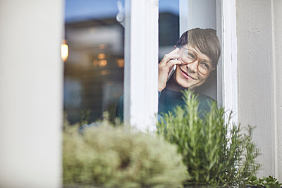 Smiling woman on the phone at home at the window - p300m2189306 by Maya Claussen