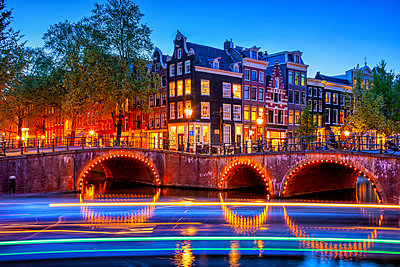 Netherlands, rth Holland, Amsterdam, Light trails in front of illuminated old town arch bridge at dusk - p300m2197150 by Artur Bogacki