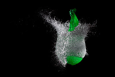 Green waterballoon bursting against black background, close up - p300m981165f by Patrick Sander