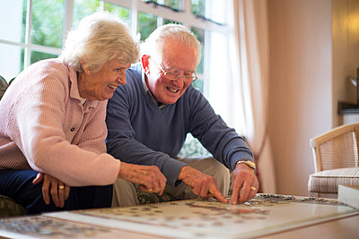 Older couple on sofa solving jigsaw puzzle - p555m1305744 by Resolution Productions