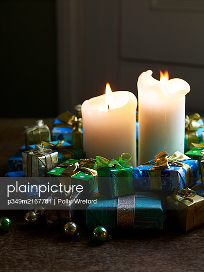 Lit candles with group of tiny presents and baubles - p349m2167781 by Polly Wreford