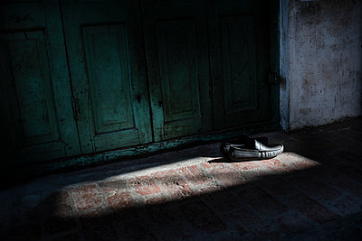 Shoes in the light in front of a door - p1007m2099039 by Tilby Vattard