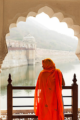 Indian woman with orange Saree below a stone arch, Jaipur - p1166m2096203 by Cavan Images
