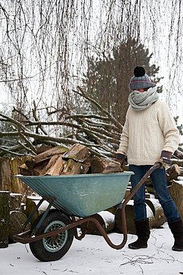 Woman walking through the snow with a wheelbarrow full of wood logs - p1231m1043134 by Iris Loonen