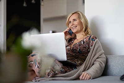 Blond woman with smartphone and laptop on couch at home - p300m2167120 by Rainer Berg
