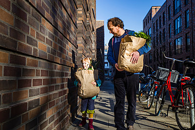 Man with daughter holding paper bag of vegetables while walking on alley - p300m2275327 by Irina Heß