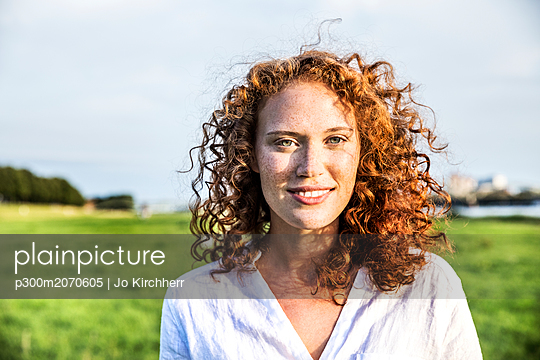 Portrait of freckled young woman with curly red hair - p300m2070605 by Jo Kirchherr