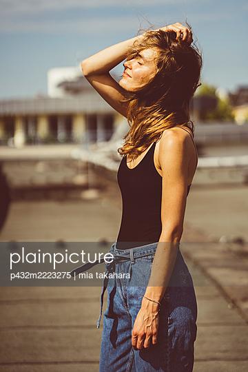 Junge Frau genießt die Sonne auf dem Hausdach - p432m2223275 von mia takahara