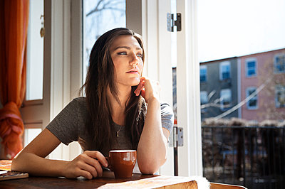 Thoughtful woman with coffee cup on table at home - p1166m1036881f by Andrew Lipovsky