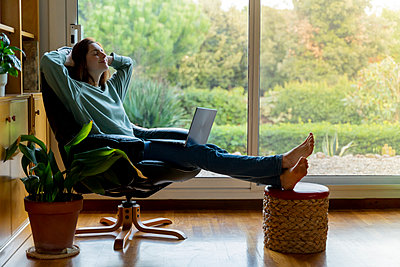 Woman with hands behind head relaxing while sitting with laptop on chair at home - p300m2264577 by VITTA GALLERY