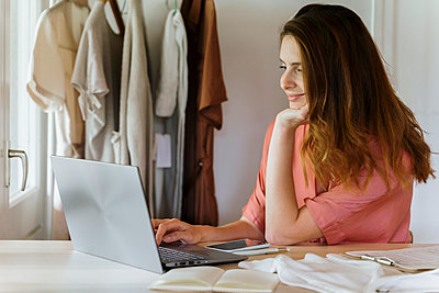 Smiling female fashion designer using laptop while working at home - p300m2287202 by VITTA GALLERY
