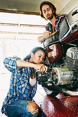 Man watching woman repairing motorcycle in garage - p555m1303791 by Peathegee Inc