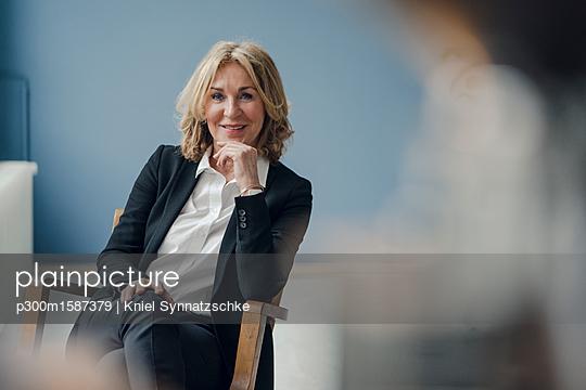 Portrait of smiling senior businesswoman sitting in chair - p300m1587379 von Kniel Synnatzschke