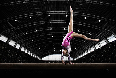 A young woman gymnast performing on the beam, balancing on her hands on a narrow piece of apparatus. - p1100m1095650 by Mint Images