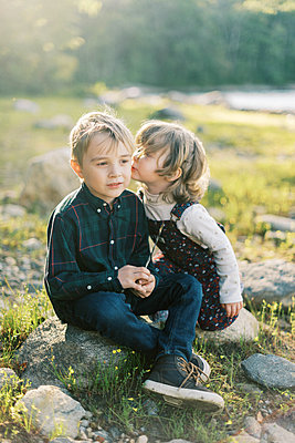 Two siblings whispering secrets to each other by the lake - p1166m2208559 by Cavan Images