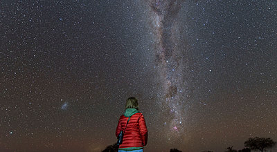 Namibia, Region Khomas, near Uhlenhorst, Astrophoto, Stargazing woman observing the Southern Cross embedded in the Milky Way band - p300m1505509 by Thomas Grohmann