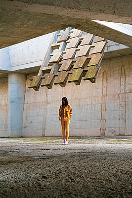 Young woman wearing yellow jeans clothes, standing in concrete building - p300m2023775 by VITTA GALLERY