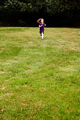 Young Girl in Purple Dress Running in Field - p694m663643 by Maria K