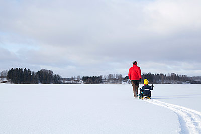 Father pulling sons along on sledge in snow covered landscape, rear view - p924m1422673 by Tiina & Geir