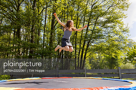 Alone on the trampoline - p076m2222361 by Tim Hoppe