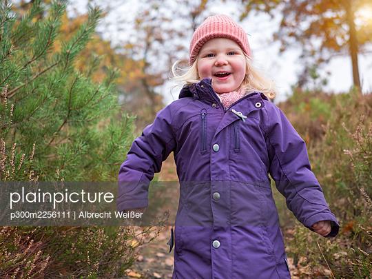 Happy cute girl in purple jacket walking by plants - p300m2256111 by Albrecht Weißer