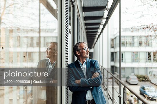 Male entrepreneur with arms crossed looking away while leaning on window in office balcony - p300m2266306 by Gustafsson