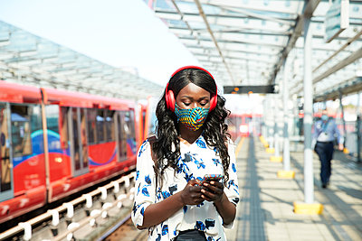 Businesswoman with face mask and headphones using mobile phone while standing at station platform - p300m2241641 by Pete Muller