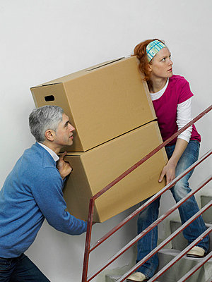 A couple carrying boxes together up stairs - p3018659f by Antenna photography