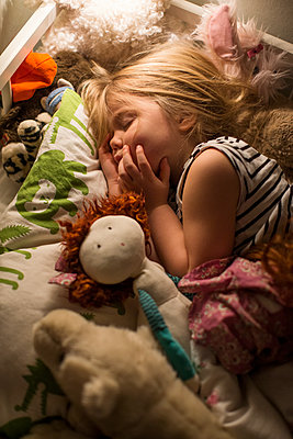 Small girl sleeping in bed - p312m1229007 by Peter Rutherhagen