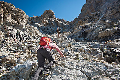 Two Friends Scramble Up A Boulder Field On Their Way To The Summit Of Middle Teton In Grand Teton National Park - p343m1217858 by Rob Hammer