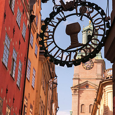 Sign on the side of a building with a clock tower in the background; stockholm sweden - p442m700449 by Keith Levit