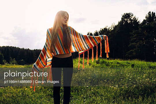Relaxed woman wearing poncho while standing on grassy field