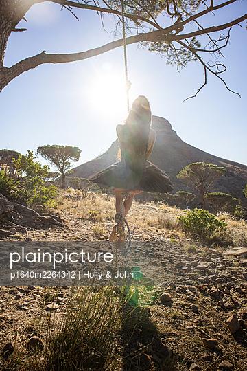 Brunette woman swings under tree - p1640m2264342 by Holly & John