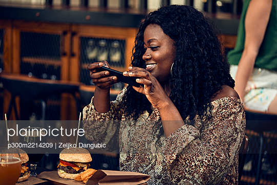 Smiling woman with smartphone having a burger in a pub - p300m2214209 by Zeljko Dangubic