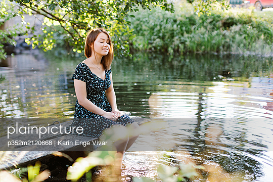 Young woman sitting by lake - p352m2120668 by Karin Enge Vivar