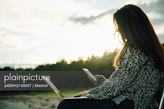 Mid adult woman with laptop text messaging while sitting at beach during sunset - p426m2149247 by Maskot