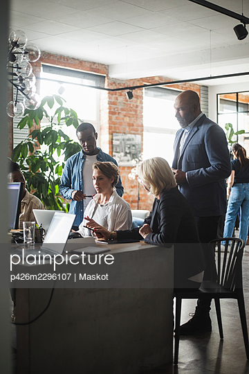 Female entrepreneur discussing over laptop at startup company - p426m2296107 by Maskot