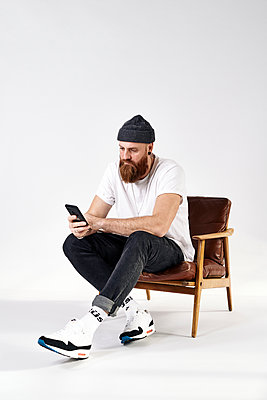 Man with full beard on armchair using smartphone - p1124m2229080 by Willing-Holtz