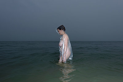 Woman in the sea, at dusk - p1132m925526 by Mischa Keijser