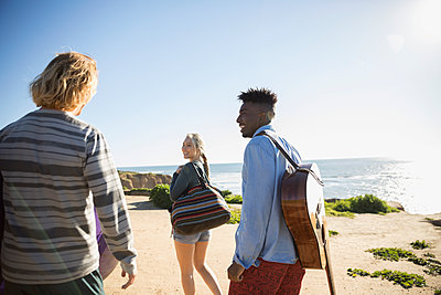 Young friends walking with guitar on sunny beach - p1192m1418566 by Hero Images