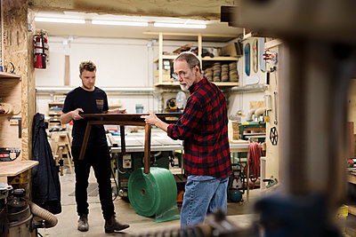Male carpenters carrying coffee table in workshop - p1192m2066865 by Hero Images