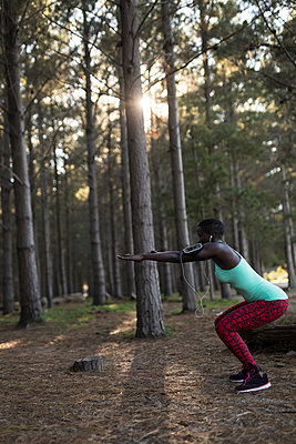 Female athlete performing squats in the forest - p1315m2003211 by Wavebreak