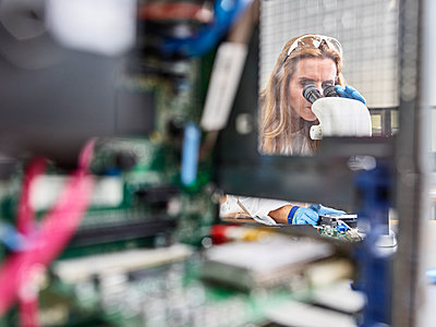 Female technician working with microscope in research laboratory - p300m2114155 by Christian Vorhofer