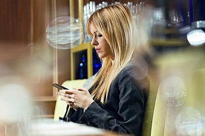 Businesswoman using cell phone in a restaurant - p300m2140177 von Josep Suria